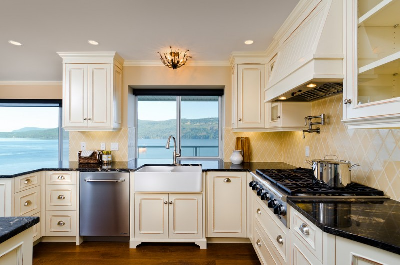 the sink glass window chandelier beige cabinets dishwasher whte double sink beige backsplash glass cabinet doors stovetop rangehood black granite countertop