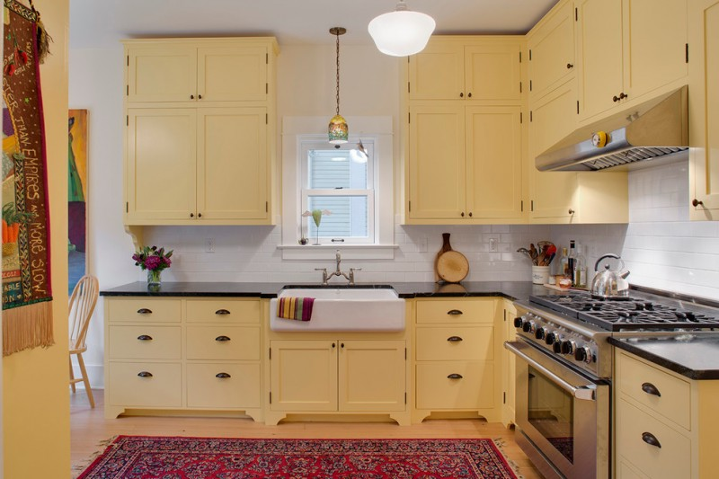 the sink small window pendant lamp range hood stovetop oven yellow cabinet white subway backsplash tile red mediterranean rug faucet