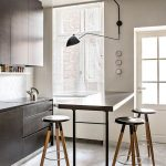 Thin Long Rectangular Table, Lanky Stools With Round Seating, Dark Cabinet, Marble Backsplash, White Wall, Windows, Marble Floor