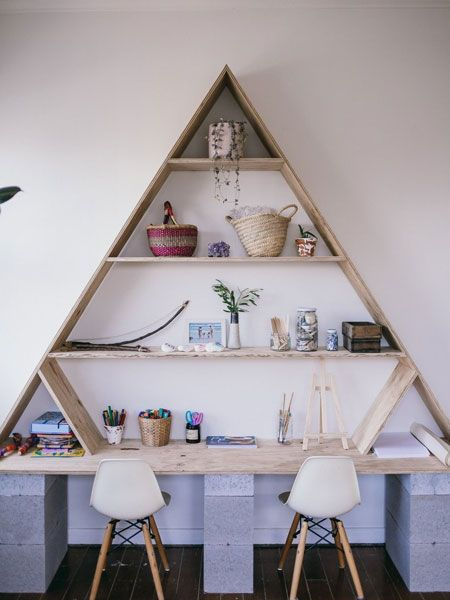 triangular shelves on top of long wooden table, white modern chairs, grey drawers