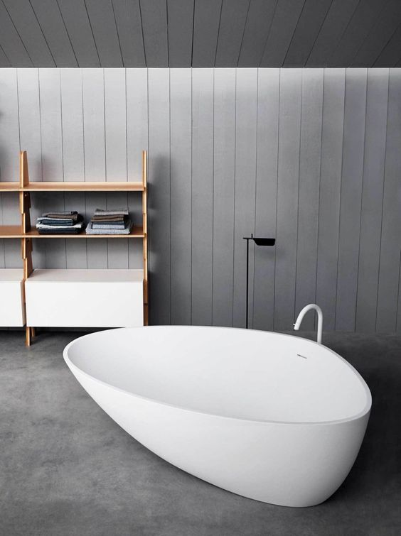 unique white tub with white faucet, grey seamless floor, grey wooden wall and ceiling, wooden shelves