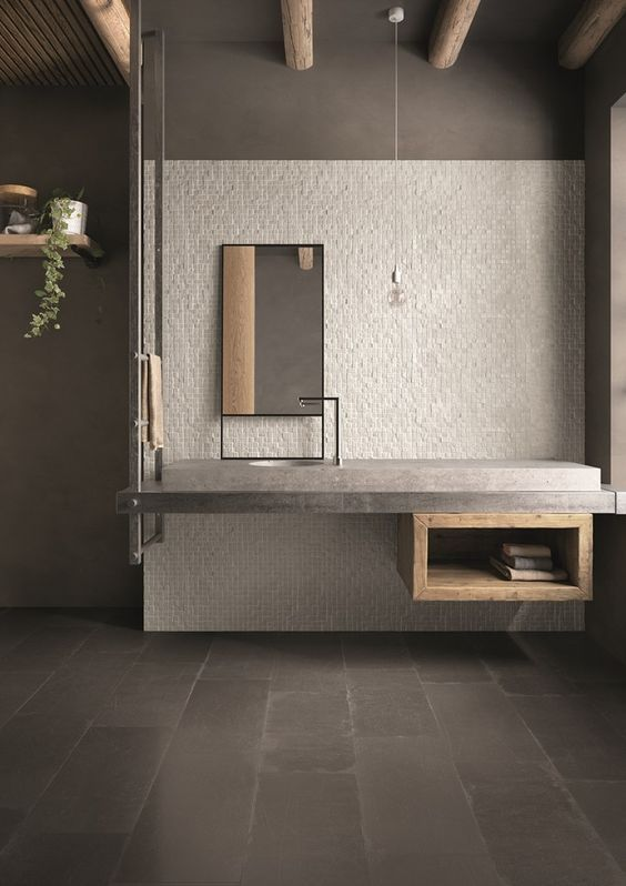 vanity with grey top, wooden shelves, grey backsplash, grey wall, pendant, mirror, thin lined faucet