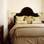 Very Narrow Bedside Table Black Headboard Wooden Dresser Gold Wall Sconces Silk Pillows Beige Beding Grey Rug White Walls Drawer