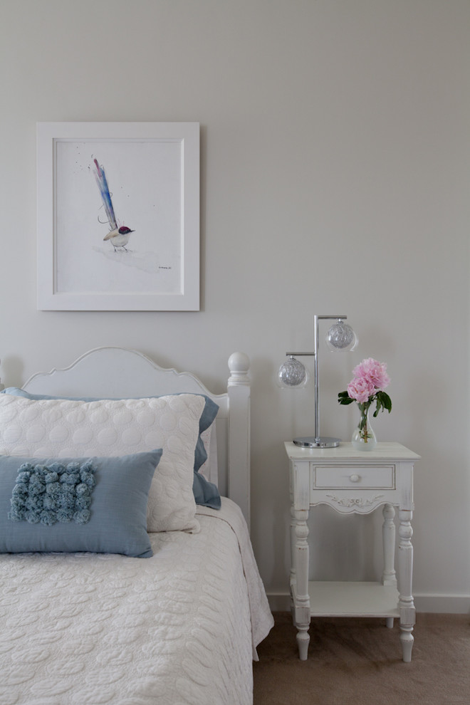 very narrow bedside table white frame white bedding blue pillows white wall drawer white headboard glass flower vase table decoration