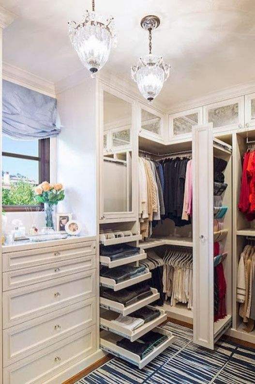walking closet, wooden floor, rug, white cupboard, shelves, open drawers, white cabinet, window, pendants