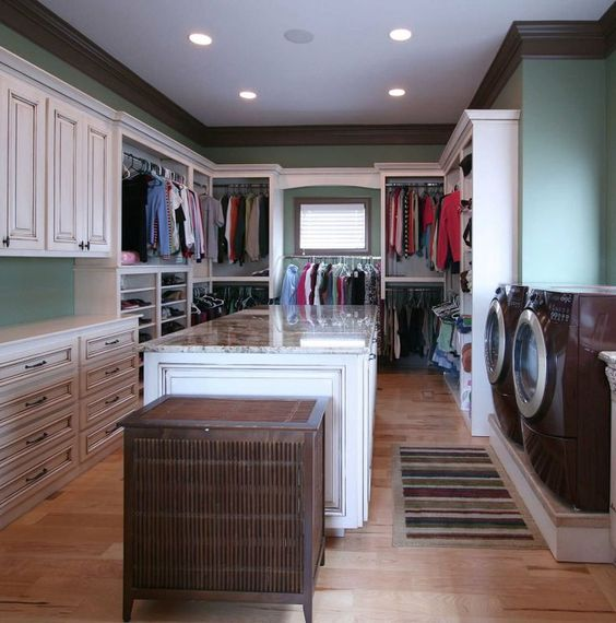 walking closet, wooden floor, white table with marble top, white built in shelves and drawers, white cabinet, two waching machines