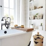 White Bathroom With White Pebbles Floor, White Built In Shelves, White Wooden Wall Planks, White Tub With Black Faucet, White Curtain, Rattan Basket
