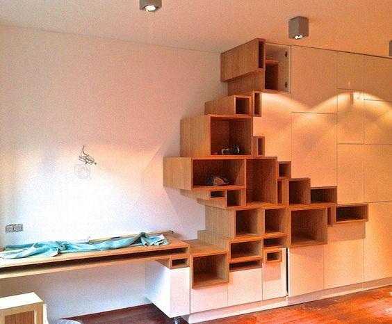 white cabinet with brown wooden shelves on the left in assymetrical position, wooden table