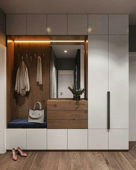 white cupboard with nook with LED lights on ceiling, mirror, hooks, wooden table