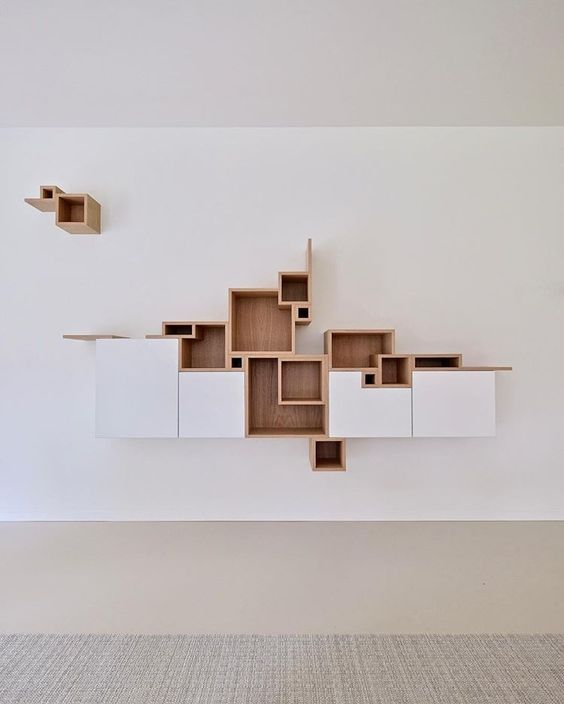 white floating cabinet with brown wooden shelves in different sizes in random arrangments