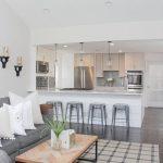 White Ktichen With Island, Grey Stools, Grey Sofa, Plaid Rug, Rectangle Coffee Table, Dark Wooden Floor