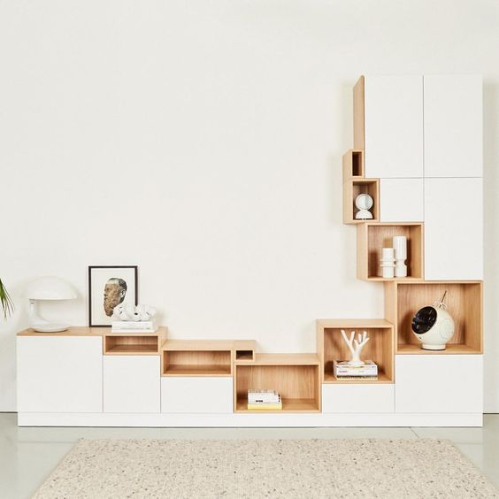 white low cabinet, different sized brown wooden shelves in jagged arrangments