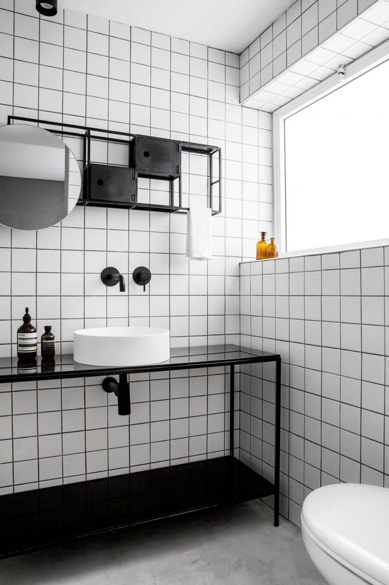 white square tiles on the wall, marble floor, black shelves vanity, black floating shelves, white round sink, round mirror, white toilet