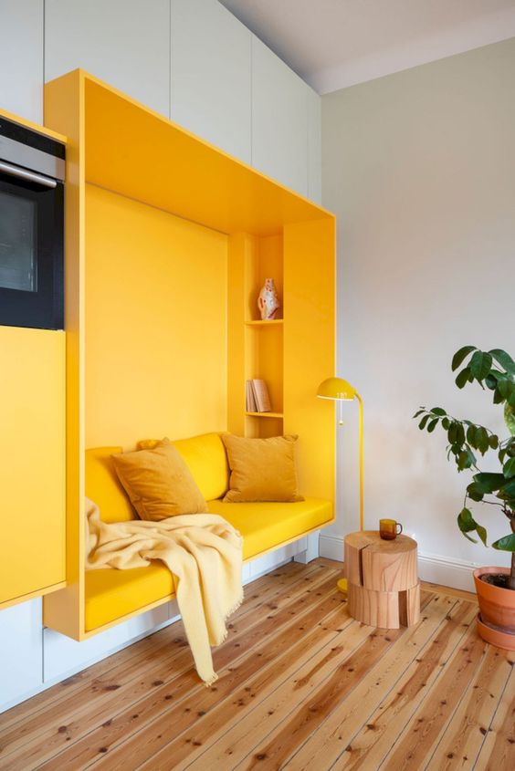 white wall with yellow nook, yellow cushion, shelves inside, yellow pillows, wooden floor, wooden side table, yellow floor lamp