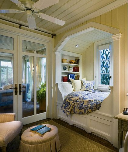 white wooden bed nook in octagonal framed, bookshelves on headboard, blue pattern bedding, near window