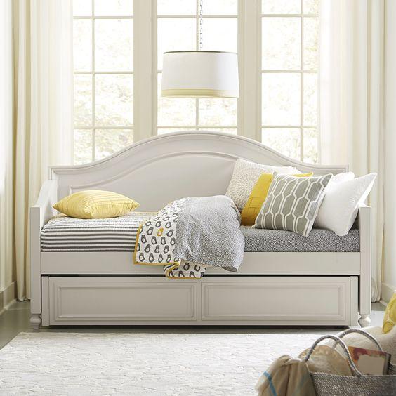 white wooden daybaed, trundle, grey cushion, white rug, white floor lamp