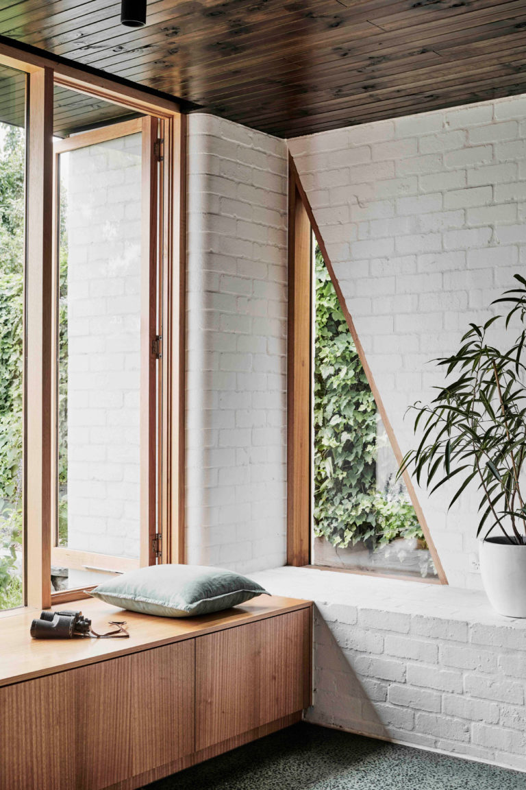 window seat, brown wooden bench, wooden framed window, white open brick wall, triangle window in the corner