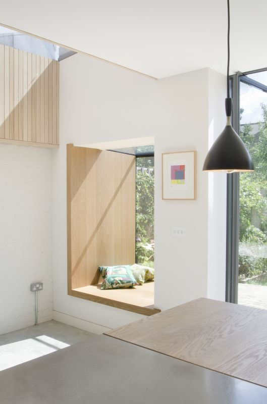 window seat, white wall, clear glass window, wooden board in L for seaing and part of the wall