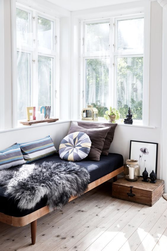 wooden bed platform, black cushion, pillows, near the window