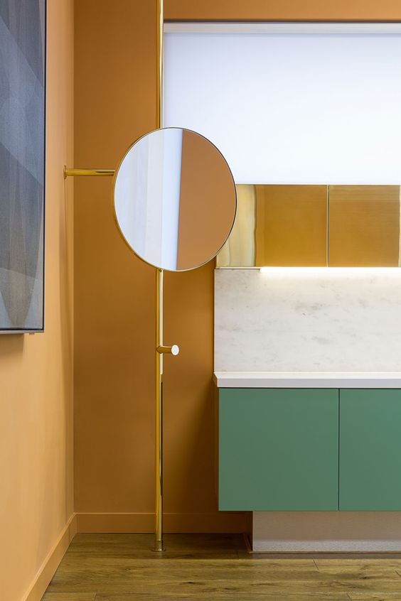 wooden floor, green floating vanity, white marble top and backsplash, yellow upper cabinet, round mirror on metal post
