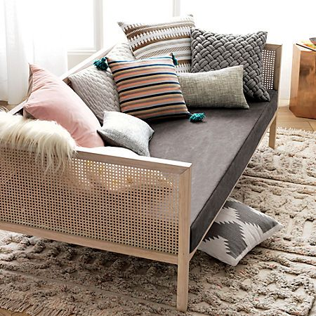 wooden rattan daybed platform, grey cushion, pillows, brown rug