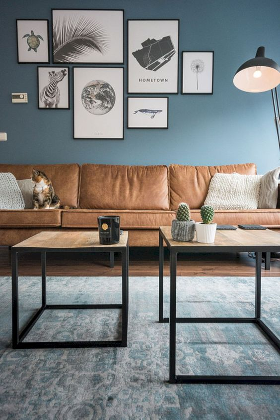living room, wooden floor, blue rug, blue wall, brown leather sofa, nesting coffee table, black floor lamp