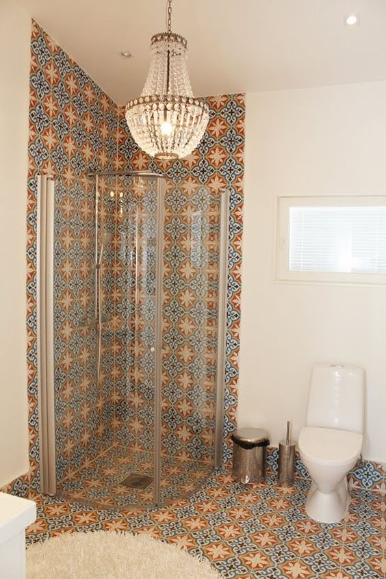 06 bright patterned tiles on the wall and floor, white wall and floor, white toilet, chandelier, glass shower partition