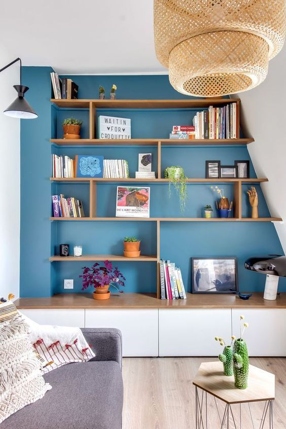 living room, wooden floor, white wall, blue painted wall inside the built in shelves, white wooden bottom cabinet, grey sofa, wooden hexagonal coffee table, rattan pendant
