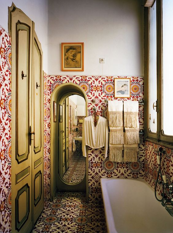 07 red patterned tiles on the wall and floor, white tub, white wall, brown wooden door, tall mirror, tall window