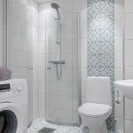 Blue Patterned Tiles On The Floor And Wall Line, Whitewall Tiles, White Toilet, White Sink, Glass Partition Shower, White Machine
