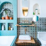 Blue Small Paterned Tiles On The Wall, Blue Heringbone Floor Tiles, Blue Herringbone Tiles On The Tub And Wall, White Toilet, Floating Vanity, Small Mirrors, White Sconce