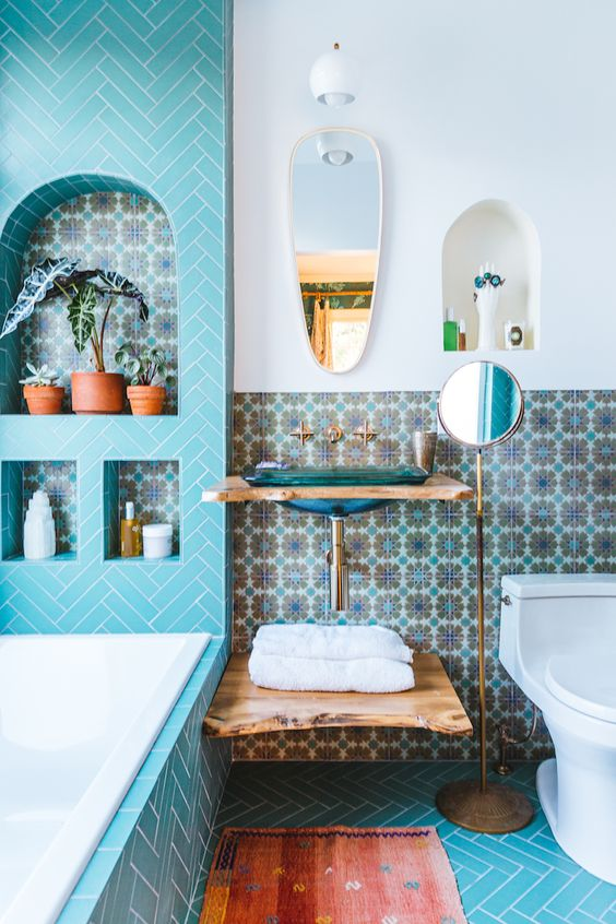 10 blue small paterned tiles on the wall, blue heringbone floor tiles, blue herringbone tiles on the tub and wall, white toilet, floating vanity, small mirrors, white sconce