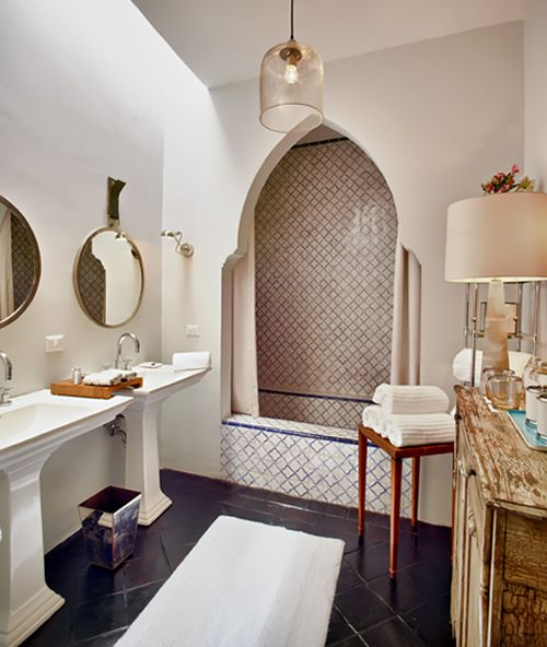 Moroccan bathroom, black tiles floor, whi sink vanity, round mirrors, clear glass cage pendant, white wall, moroccan arch, square tiny tiles for shower area, curtain, wooden cabinet