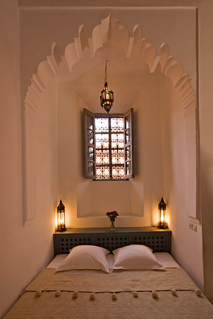Moroccan bedroom with detailed arch, moroccan pendants, moroccan windows, table headboard, beige bedding