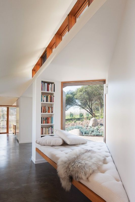 Sloping Wall, floating wooden bench, white cushion, white pillows, builtin shelves, large windows