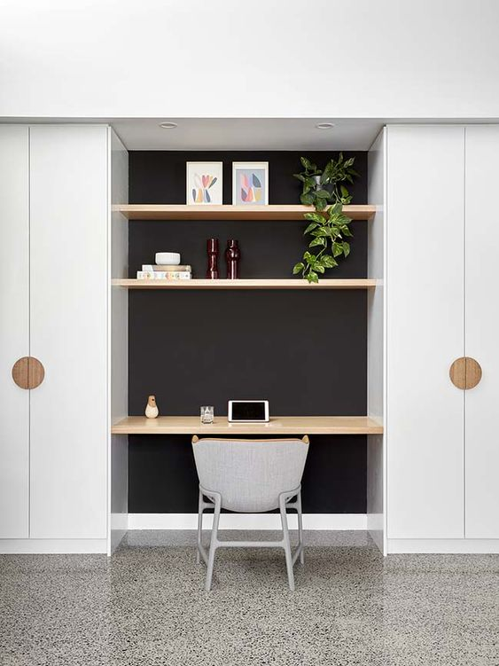 alcove between white cupboardm dark wall, wooden floating shelves, wooden floating table, white modern chair