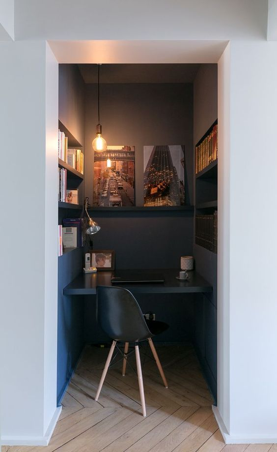 alcove room, dark blue wall, dark blue floating table, built in shelves, pendant, black midcentury modern chair