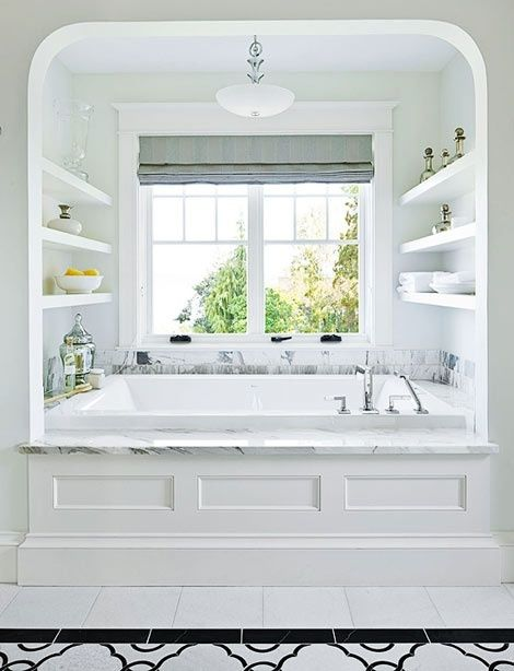 alcove, white wall, white floating shelves, white marble top, white tub, white black patterned floor bathroom floor