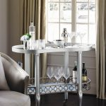 Bar Server Furniture Dark Flooring Tan Curtains Glass Window Silver Bar Cart Wheels Gray Chair Glass Bottle Wine Glasses