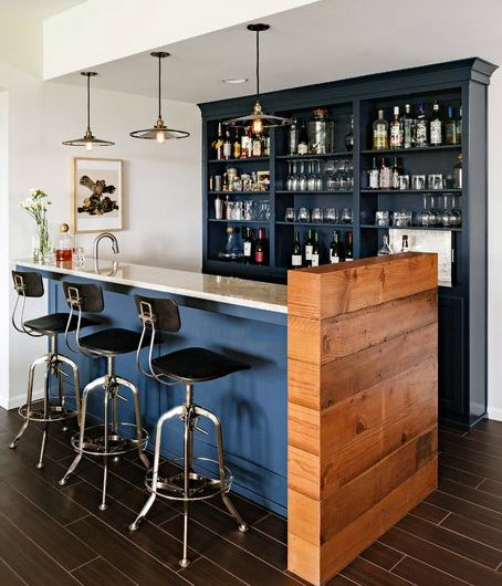 bar with dark blue shelves on the back, wooden floor tiles, blue island with white top, wooden partition, pendants, black steel stools