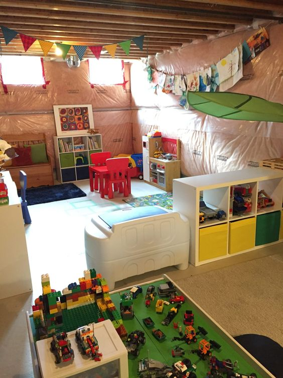 basement, brown floor, brown wall, white low bookshelves, low colorful table chair, mat, toys