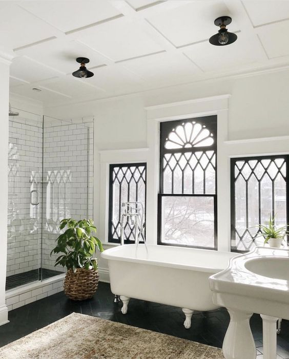 bathroom, black herringbone tile floor, white wall, white tub, white sink, white subway wall on shower area, black ceiling pendant