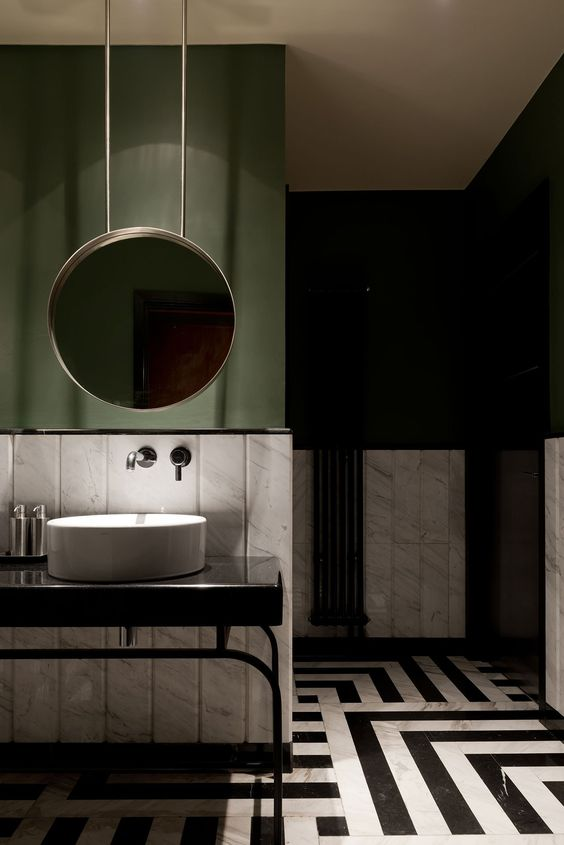 bathroom, black white unique floor tiles, white backsplash wall, dark green painted wall, round mirror, white round sink