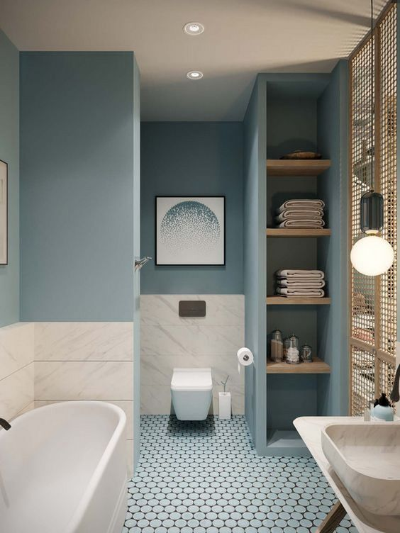 bathroom, blue wall, blue tiny hexagonal floor tiles, blue built in shelves, white floating toilte, white tub, white marble, white marble sink, pendant