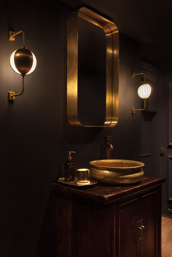 bathroom, brown floor tiles, wooden cabinet, golden sink, golden mirror, golden sconces