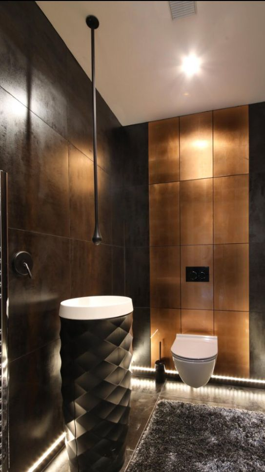 bathroom, dark grey floor, dark grey wall tiles, dark acorn shaped vanity and white sink, white toilet, golden statement wall