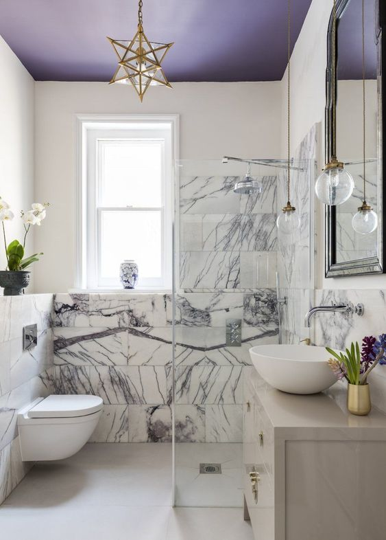 bathroom, grey floor, white toilet, grey vanity with marble top, beige wall, star pendant, clear bulb pendants