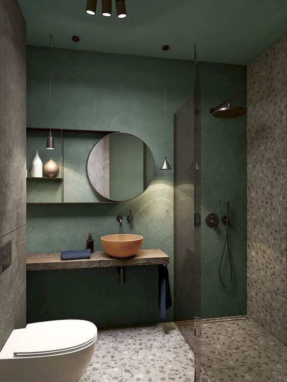bathroom, grey terrazzo floor and wall tiles, green painted wall, round mirror, floating vanity, orange round sink, round mirror, grey wall, white floating toilet