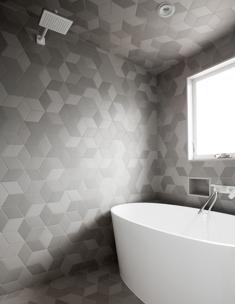 bathroom, hexagonal tiles on the entire wall, white tub, white shower faucet