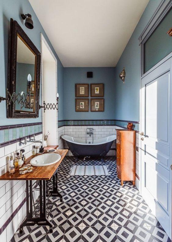 bathroom, patterned floor tiles, blue wall, white backsplash, white painted door, mirror, wooden vanity, white sink, black sink